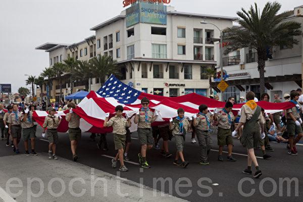 7月4日亨廷顿海滩市全美第三大的国庆游行,全长达到4英里,参与观众人山人海估计多达数十万。图为童子军拉开巨幅国旗走在队伍前面。(摄影:季媛/大纪元)
