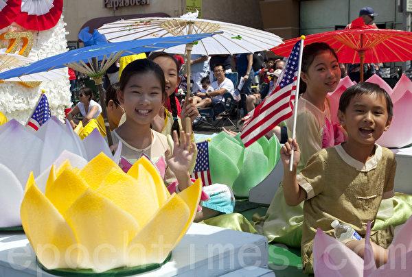 法轮功小弟子,坐在学员亲手制作的莲花花车上兴奋参与游行。(摄影:季媛/大纪元)