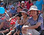 香港移民Peter Ng一家開心地觀看列治文國慶遊行,慶賀加拿大國慶節。(攝影:邱晨/大紀元)