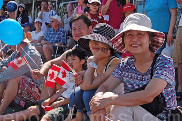 香港移民Peter Ng一家开心地观看列治文国庆游行,庆贺加拿大国庆节。(摄影:邱晨/大纪元)