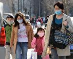 图:根据一项追踪20年的研究报告,中国北方冬天烧煤取暖引起的空气污染,造成平均人口寿命比南方要低5.5年。图为北京街头带着口罩的行人。(AFP)