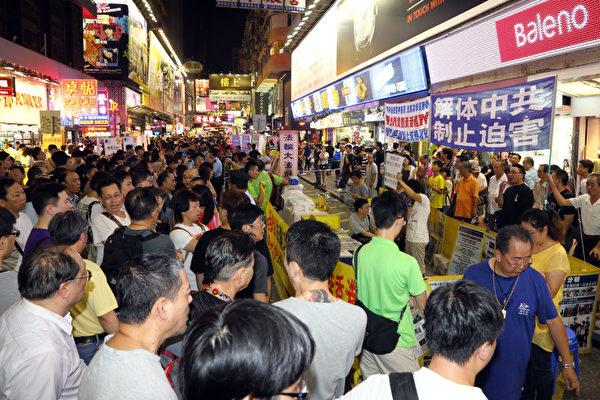 由于中共江泽民集团的走狗梁振英的垂死挣扎,香港青关会恶徒7月14日再次暴力骚扰位于旺角行人专用区的法轮功真相点,上演了一场正邪大战;大批香港市民涌上街头,纷纷怒斥中共青关会的邪恶行径以及警方的纵容,图为现场香港民众愤怒谴责受地下党特首梁振英操控的青关会组织头目们。(摄影:潘在殊/大纪元)