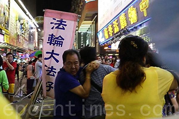 黑帮青关会头目林国安(左一,蓝衫者)勒住一名市民脖子,女恶霸肖小容(右一,黄衫者)则用脚狠踢,部分法轮功学员也被恶徒殴打。(摄影:潘在殊/大纪元)