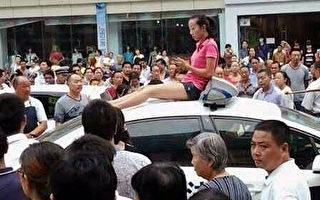 城管打傷司機 妻子持刀爬警車抗議 千人聲援(組圖)