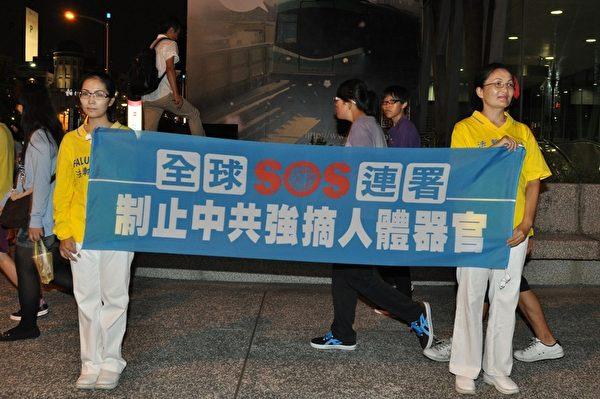 2013年7月20日,法輪功學員在街頭拉橫幅,向往來民眾講活摘器官真相。(李晴玳/大紀元)