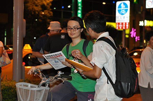 2013年7月20日,法輪功學員向過往民眾徵簽,邀請正義力量支持,共同制止中共活摘器官暴行。(李晴玳/大紀元)