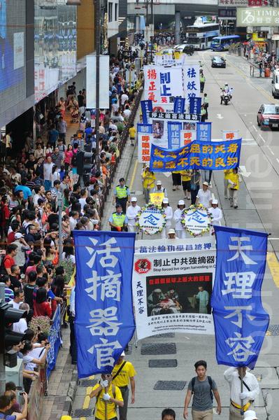 香港法輪功學員21日在長沙灣舉行舉行7.20法輪功反迫害14週年集會遊行,隊伍聲勢浩大沿途吸引許多中港民眾觀看。(宋祥龍/大紀元)