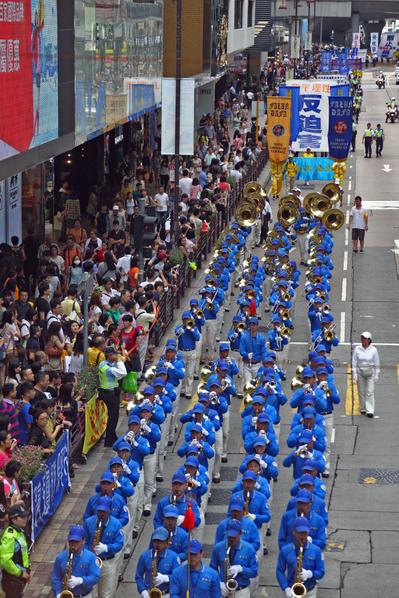 香港法輪功學員7月21日舉行反迫害集會遊行,約八百人的遊行隊伍,在天國樂團的領頭下,途經九龍區鬧市前往尖沙嘴天星碼頭,各式展現法輪大法美好和揭露中共暴行的旗旛和橫幅,沿途吸引許多香港市民及大陸民眾觀看。(攝影:潘在殊/大紀元)