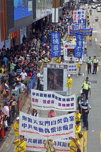 香港法輪功學員7月21日舉行反迫害集會遊行,約八百人的遊行隊伍,在天國樂團的領頭下,途經九龍區鬧市前往尖沙嘴天星碼頭,各式展現法輪大法美好和揭露中共暴行的蕃旗和橫幅,沿途吸引許多香港市民及大陸民眾觀看。(攝影:潘在殊/大紀元)