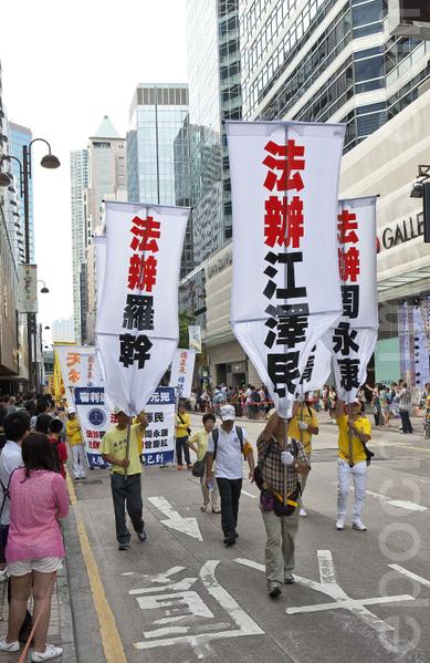 香港法輪功學員21日在長沙灣舉行7.20法輪功反迫害14週年集會遊行,隊伍聲勢浩大沿途吸引許多中港民眾觀看。(攝影:余鋼/大紀元)