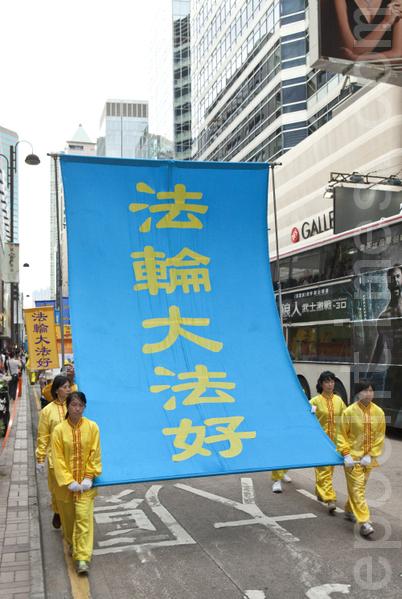 香港法輪功學員21日在長沙灣舉行舉行7.20法輪功反迫害14週年集會遊行,隊伍聲勢浩大沿途吸引許多中港民眾觀看。(攝影:余鋼/大紀元)