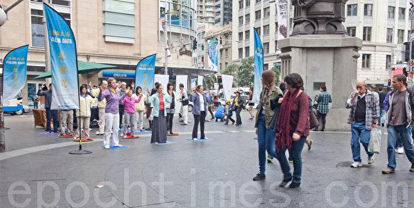 7月20日,在悉尼市中心的著名商业中心QVB(维多利亚女皇大厦)门前,法轮功学员进行功法示范展示,吸引了澳洲人的关注。(袁丽/大纪元)