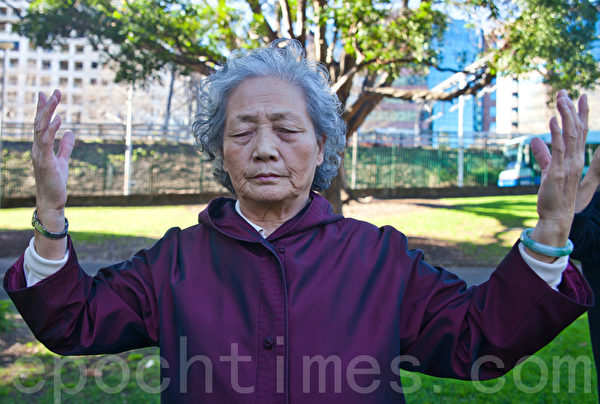 """2013年7月20日,在""""720""""14周年反迫害的活动中,悉尼法轮功学员在悉尼中央火车站对面的拜尔默公园炼功。图为法轮功学员陶月芳女士。(袁丽/大纪元)"""