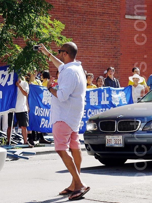 2013年7月20日法輪功學員在芝加哥中領館前集會,路人拍照。(攝影:溫文清/大紀元)