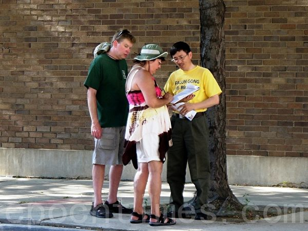 2013年7月20日法輪功學員在芝加哥中領館前集會,來自伊州香檳市的大學教授馮先生向路人徵簽,支持美國國會281號決議案。(攝影:溫文清/大紀元)