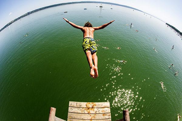 德国南部小镇乌廷,一男子纵身一跃,消失在碧绿的阿默湖中。德国持续高温的天气,最高气温达到30摄氏度。(MARC M‹LLER/AFP)