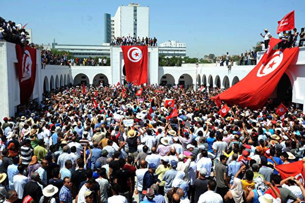 突尼斯,大量民众参加反对派领袖布拉赫米(Mohamed Brahmi)的葬礼。几天前,布拉赫米在家外被歹徒袭击,中14枪身亡。凶手使用的手枪,在五个月前也曾被用来枪杀另一名反对派领袖。对此事件,突尼斯官方把罪责归咎于勾结基地组织的极端分子。(FETHI BELAID/AFP)