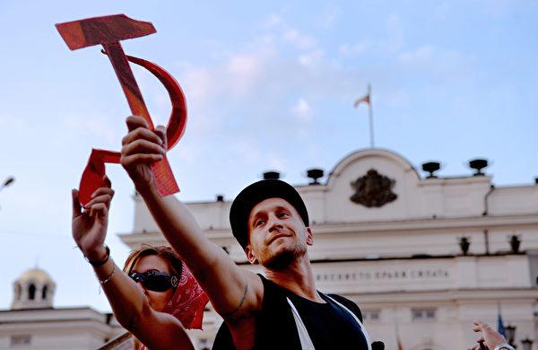 保加利亚首都索非亚,手拿镰刀、铁锤的男女出现在集会的民众之中,抗议堕落、低效的现政府面对每况日下的国民经济而无作为。前共产主义国家保加利亚,2012年度人均国内生产总值世界排名78,是欧盟中最穷的国家。(DIMITAR DILKOFF/AFP)