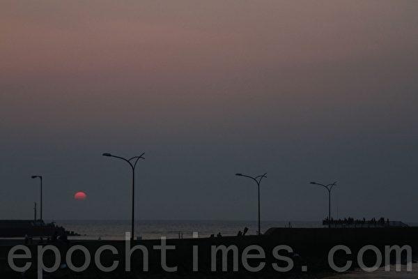 夕阳、沙滩、海浪、风车,这样幽美的景致让单车骑士着迷。(摄影:许享富 /大纪元)