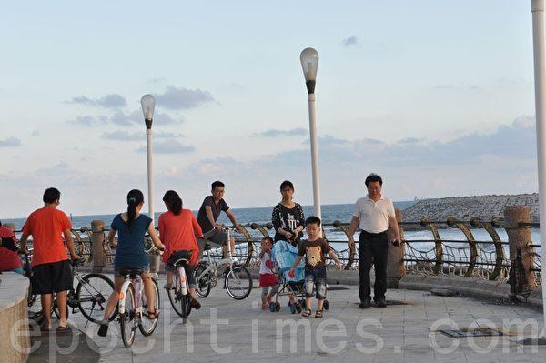 在海岸自行车道踩风,或三五好友结伴同行,或阖家亲子共游。(李晴玳/大纪元)