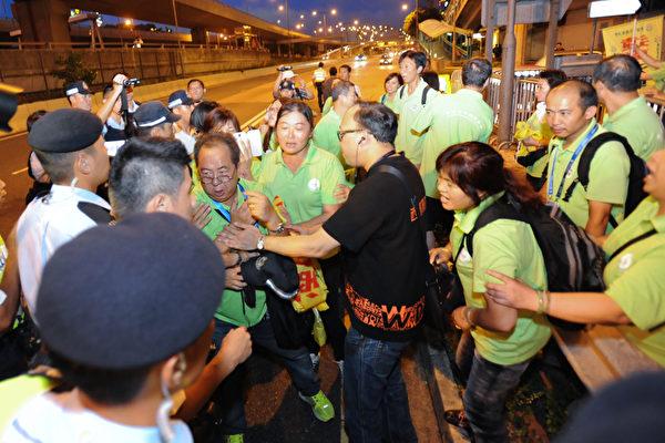 香港法輪功學員於中共迫害法輪功14周年之際,到中聯辦外靜坐。期間,香港青年關愛協會(青關會)到場滋擾,更一度與警方發生衝突。(大紀元資料圖片)