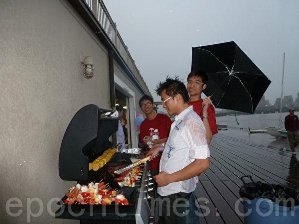 (左起)万马奔腾计划青年曾灏、萧立勋和义工黄士弘冒雨为大家烧烤服务。(摄影﹕苏仪/大纪元)