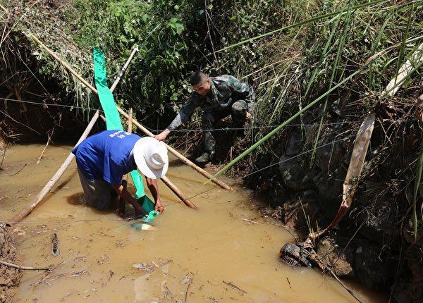 据当地有关部门统计,湖南省境内452条溪河断流,476座小型水库、10.21万处山塘干涸,蓄水每天减少1.8亿立方米。 图为一农户尝试从尚未干枯的水塘抽水灌溉农田。(ChinaFotoPress/Getty Images)