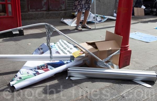 立式橫幅被掀翻在地,支撐桿被折。(攝影:冠齊/大紀元)