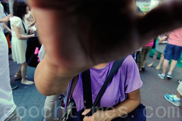 11日下午旺角一名老妇趁派发员工离开时,偷取一大叠报纸,还用手遮住摄影记者拍摄。(宋祥龙/大纪元)