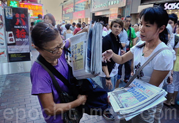 大紀元從旺角上架以來,中共外圍組織青關會一直雇用人偷取大紀元報紙。圖為11日下午一名老婦趁派發員工離開時,偷取一大疊報紙。(宋祥龍/大紀元)