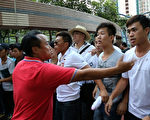 醜聞纏身民望不斷跌落的香港特首梁振英8月11日到天水圍出席地區論壇,多個政黨和團體到場示威抗議,場內場外都有黑幫成員護駕,圖為香港元朗美都餐廳及龍獅隊負責人陳嘉輝(紅衫者)和香港屏山鄉鄉委會主席曾樹和(草帽者)現場指揮黑道人士圍毆抗議人士。香港政壇元老李柱銘籲港人別再沉默、斥梁振英黑幫亂港。(潘在殊/大紀元)