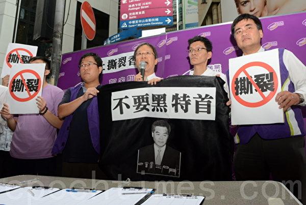 """公民党撕破象征""""黑势力、黑特首""""的黑布,抗议特首撕裂香港社会,要求靠黑社会撑腰的梁振英下台。(邝天明/大纪元)"""