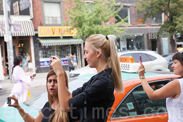遊行沿途吸引各族裔市民和遊人駐足觀看,不少民眾拿出手機拍攝。(艾文/大紀元)