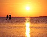 德國北部呂根島,一對夫婦在夕陽籠罩下的波羅的海中盪舟。(CHRISTOF STACHE/AFP)