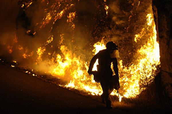 西班牙西北部山村Barbudo,漫山野火熊熊燃燒,消防員時至凌晨仍堅守火場。攝影於2013年9月5日。(MIGUEL RIOPA/AFP)