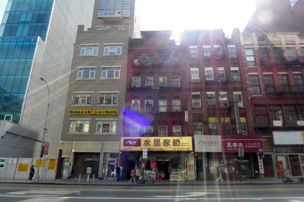 """曼哈顿、皇后区和布碌崙,罐头沙丁鱼似的""""散仔馆""""就藏身于居民楼中。图中右侧包厘街81号四楼的散仔馆因消防安全隐患多次被楼宇局、消防局查封,左侧包厘街91号蓝色玻璃幕墙所在为近两年由华埠旧楼改建的四星级酒店。(摄影:蔡溶/大纪元)"""