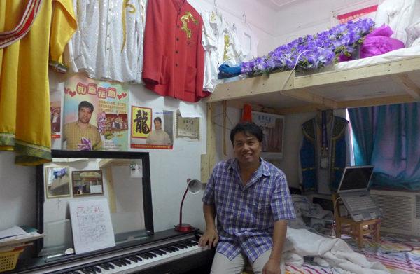 """在唐人街以当司仪和唱歌为生的黄云秀,经过十多年的努力,终于不再与人分租,租下这间""""最大的""""小单间,支上他的电子琴,手提电脑则以小凳子为桌,架在床上。(摄影:蔡溶/大纪元)"""
