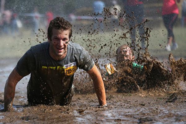 當地時間2013年9月21日,法國貝內舉行泥漿挑戰賽,參賽選手要跑完全程13公里的障礙賽。(KENZO TRIBOUILLARD/AFP)