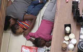 肯尼亚一家购物商城于2013年9月21日,遭数十名来自索马里的武装份子攻击。军方与暴徒对峙30多小时后,于22日加强武力展开攻坚并救出大部分人质。图为法新社于22日拍摄到商城吧台旁,1名妇女和2名儿童趴地躲在墙边。(摄影:Nichole Sobecki/AFP/Getty Images)