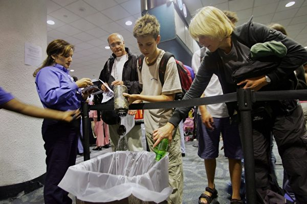 MIAMI - AUGUST 10: Joe Weber (2nd R) and his mother Ellen Weber (R) dump water into a waste basket after removing the liquid products from their carry on luggage at the Miami International Airport August 10, 2006 in Miami, Florida. U.S. airports stepped up security after British police allegedly thwarted a major terrorist plot to blow up aircraft flying between Britain and the United States. (Photo by Joe Raedle/Getty Images)