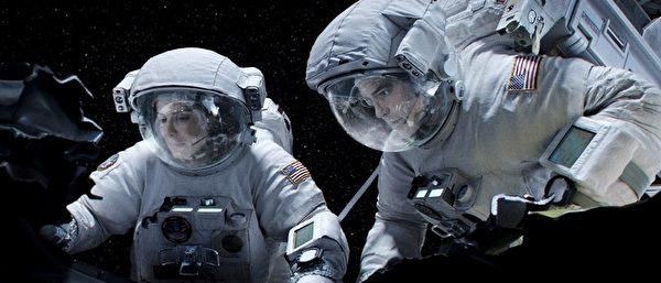 珊卓•布拉克与乔治•库隆尼在《地心引力》中的剧照。(华纳兄弟提供)