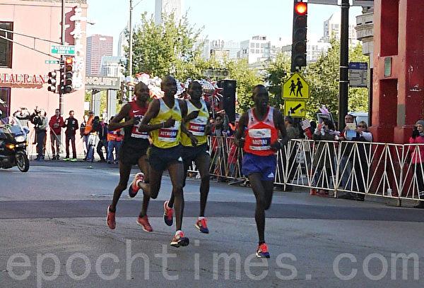 着黄色球衣后面选手为男子组冠军,来自肯尼亚的Dennis Kimetto。(摄影:温文清/大纪元)