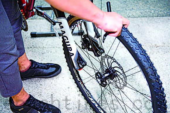 正将自行车轮胎卸下。(庄孟翰/大纪元)
