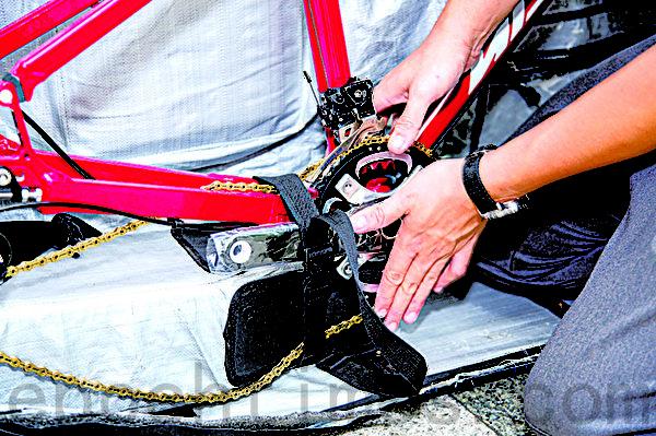 利用自行车携行袋内的软垫将自行车车身架高,保护与固定车盘。(庄孟翰/大纪元)