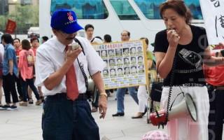 同心會會長周慶峻(左)、成員張秀葉(右)在台北101大樓前謾罵法輪功學員。(Ke-Ren/大紀元)
