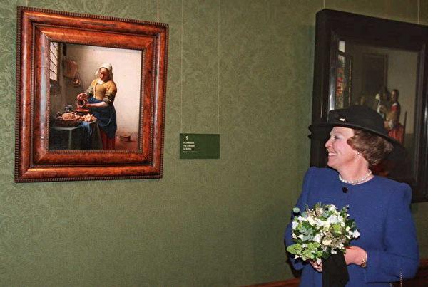 荷蘭女王貝婭特麗克絲(Beatrix),站在約翰尼斯‧維米爾的(Johannes Vermeer)知名畫作「倒牛奶的女僕」(The Milkmaid)油畫前觀賞大師傑作。(AFP)