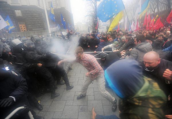 乌克兰24日约有5万民众上街抗议,遭到警方以催泪瓦斯和警棍驱赶。(GENYA SAVILOV/AFP)