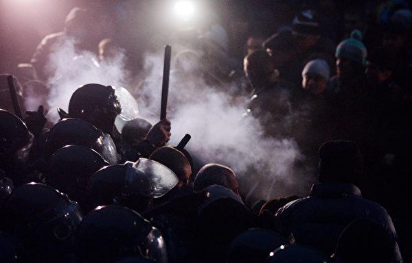 乌克兰24日约有5万民众上街抗议,遭到警方以催泪瓦斯和警棍驱赶。(SERGEI SUPINSKY/AFP)