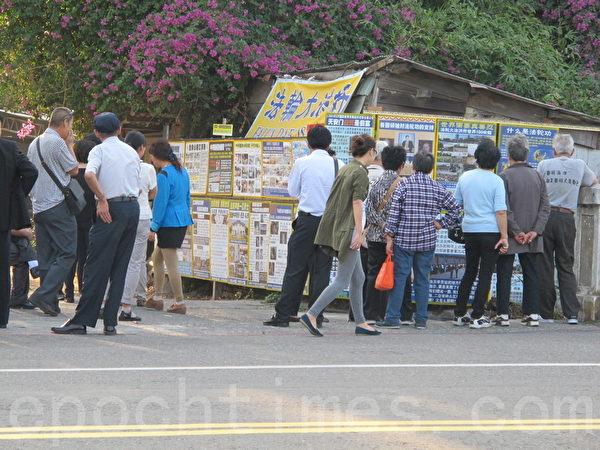 大陆游客造访台湾景点,细看法轮功学员真相展板,了解法轮大法好,以及中国共产党假恶斗本质,都纷纷主动三退。(廖凤琳/大纪元)