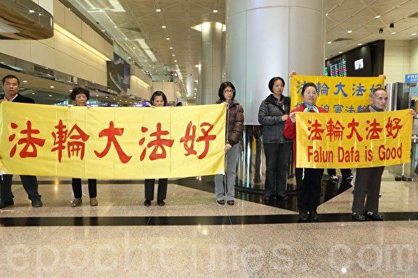 60多名法轮功学员到机场拉横幅反迫害,要中共立即停止迫害法轮功(林仕杰 /大纪元)